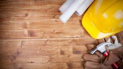 Casco-de-obra-amarillo-planos-y-unos-guantes-y-un-martillo-sobre-una-mesa-de-madera